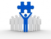 Leader holding blue jigsaw piece next to line of human forms on white background